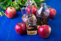 Ξίδι μηλίτη της Apple Μπουκάλι γυαλιού τρία στο μπλε υπόβαθρο κόκκινο μήλων Στοκ Φωτογραφίες