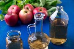 Ξίδι μηλίτη της Apple Μπουκάλι γυαλιού τρία στο μπλε υπόβαθρο κόκκινο μήλων Στοκ εικόνες με δικαίωμα ελεύθερης χρήσης