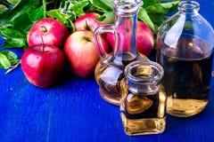Ξίδι μηλίτη της Apple Μπουκάλι γυαλιού τρία στο μπλε υπόβαθρο κόκκινο μήλων Στοκ φωτογραφία με δικαίωμα ελεύθερης χρήσης