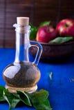 Ξίδι μηλίτη της Apple στο μπουκάλι γυαλιού στο μπλε υπόβαθρο Κόκκινα μήλα στο καφετί κύπελλο Στοκ φωτογραφίες με δικαίωμα ελεύθερης χρήσης