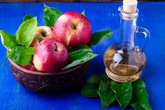 Ξίδι μηλίτη της Apple στο μπουκάλι γυαλιού στο μπλε υπόβαθρο Κόκκινα μήλα στο καφετί κύπελλο Στοκ Εικόνες