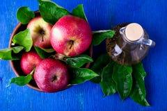 Ξίδι μηλίτη της Apple στο μπουκάλι γυαλιού στο μπλε υπόβαθρο Κόκκινα μήλα στο καφετί κύπελλο Τοπ όψη Στοκ Εικόνες