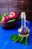 Ξίδι μηλίτη της Apple στο μπουκάλι γυαλιού στο μπλε υπόβαθρο Κόκκινα μήλα στο καφετί κύπελλο Στοκ φωτογραφία με δικαίωμα ελεύθερης χρήσης