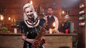 Ξανθά θηλυκά παιχνίδια μουσικών εναρέτως σε ένα saxophone απόθεμα βίντεο