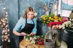 Ξανθά θηλυκά τέμνοντα κακά λουλούδια στην αγορά λουλουδιών Στοκ εικόνα με δικαίωμα ελεύθερης χρήσης