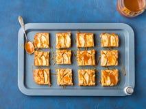 Ξανθά brownies της Apple με την καραμέλα στο μπλε υπόβαθρο δίσκων Στοκ εικόνα με δικαίωμα ελεύθερης χρήσης