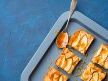 Ξανθά brownies της Apple με την καραμέλα στο μπλε υπόβαθρο δίσκων Στοκ φωτογραφία με δικαίωμα ελεύθερης χρήσης