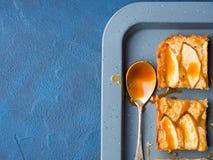 Ξανθά brownies της Apple με την καραμέλα στο μπλε υπόβαθρο δίσκων Στοκ Εικόνες