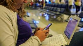 Ξανθές εργασίες κοριτσιών κινηματογραφήσεων σε πρώτο πλάνο για το lap-top Iphone στα γόνατα στον αερολιμένα απόθεμα βίντεο