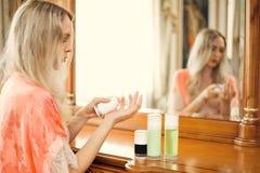 Ξανθές συμπιέσεις κοριτσιών η κρέμα από το μπουκάλι στοκ εικόνα