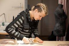 Ξανθές seamstress γυναικών περικοπές από το σχέδιο εγγράφου τεχνών για την παραγωγή των ενδυμάτων στοκ φωτογραφίες