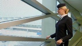 Ξανθή αεροσυνοδός που στέκεται στη αίθουσα αναμονής πριν από την πτήση στο εσωτερικό απόθεμα βίντεο