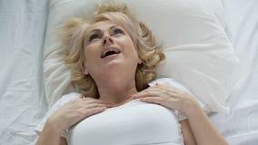Ξανθή ανώτερη γυναίκα που ξυπνά επάνω και σχετικά με στο πρόσωπό της, επίδραση μασκών, skincare απόθεμα βίντεο