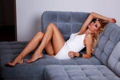 Ξανθή γυναίκα γοητείας που βρίσκεται σε έναν καναπέ Στοκ Φωτογραφία