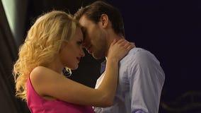 Ξανθή γυναίκα και ελκυστικός άνδρας κατά την ημερομηνία που αγκαλιάζουν, αυτί της γυναίκας φιλήματος ανδρών, πάθος φιλμ μικρού μήκους