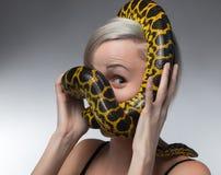 Ξανθή γυναίκα και κίτρινο anaconda στραγγαλισμού Στοκ Εικόνες