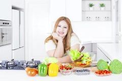 Ξανθή γυναίκα με τα λαχανικά στην κουζίνα Στοκ εικόνα με δικαίωμα ελεύθερης χρήσης