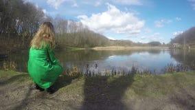 Ξανθή γυναίκα με τα πράσινα πουλιά παπιών παλτών ταΐζοντας κοντά στη λίμνη 4K φιλμ μικρού μήκους