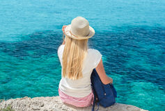 Ξανθή γυναίκα με τη συνεδρίαση σακιδίων πλάτης στον απότομο βράχο επάνω από τη θάλασσα Στοκ Φωτογραφία