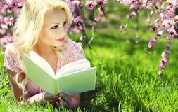 Ξανθή γυναίκα με το βιβλίο κάτω από το άνθος κερασιών Στοκ Εικόνες