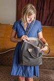 Ξανθή γυναίκα με το γκρίζο πορτοφόλι δέρματος Στοκ Εικόνες