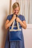 Ξανθή γυναίκα με το μπλε πορτοφόλι δέρματος Στοκ Εικόνες