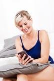 Ξανθή γυναίκα με το τηλέφωνο στο καθιστικό. Στοκ φωτογραφία με δικαίωμα ελεύθερης χρήσης
