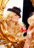 Ξανθή γυναίκα μόδας με το καπέλο στον καθρέφτη Στοκ Εικόνες