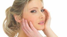 Ξανθή γυναίκα ομορφιάς σχετικά με το πρόσωπό της φιλμ μικρού μήκους