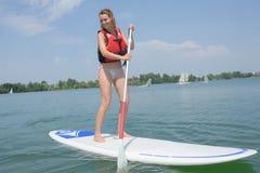 Ξανθή γυναίκα που απολαμβάνει τη στάση επάνω στη σύνοδο κουπιών για τη λίμνη Στοκ Εικόνα