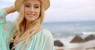 Ξανθή γυναίκα που απολαμβάνει το αεράκι στην ακτή φιλμ μικρού μήκους