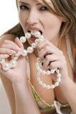 Ξανθή γυναίκα που δαγκώνει ένα περιδέραιο μαργαριταριών στοκ φωτογραφία