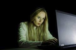 Ξανθή γυναίκα που εργάζεται σε έναν υπολογιστή τή νύχτα Στοκ Φωτογραφίες