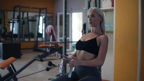 Ξανθή γυναίκα που κάνει την κατάρτιση μυών στη γυμναστική Αθλητής που επιλύει στη γυμναστική με το τράβηγμα του βάρους σε έναν εκ απόθεμα βίντεο