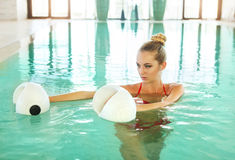Ξανθή γυναίκα που κάνει τη αερόμπικ aqua με τους αλτήρες αφρού στην κολύμβηση Στοκ εικόνες με δικαίωμα ελεύθερης χρήσης