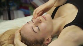 Ξανθή γυναίκα που κάνει το μόνος-μασάζ, του προσώπου μασάζ που βρίσκεται στο κρεβάτι στο σπίτι απόθεμα βίντεο