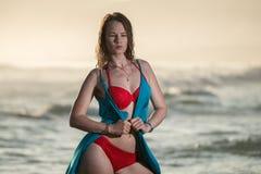 Ξανθή γυναίκα που κολυμπά στον ωκεανό με ένα κόκκινο μπικίνι Στοκ Φωτογραφία