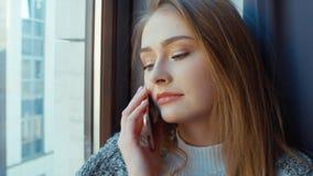 Ξανθή γυναίκα που μιλά στο τηλέφωνο από το παράθυρο απόθεμα βίντεο