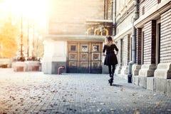 ξανθή γυναίκα που οδηγά το ηλεκτρικό μηχανικό δίκυκλο στη σύγχρονη πόλη Καθιερώνουσα τη μόδα γυναίκα που χρησιμοποιεί τη σύγχρονη Στοκ εικόνες με δικαίωμα ελεύθερης χρήσης