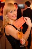 Ξανθή γυναίκα που παρουσιάζει τα εισιτήρια για ένα θέατρο ή μια συναυλία Στοκ Φωτογραφία