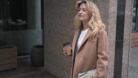 Ξανθή γυναίκα που περπατά με τον καφέ στην οδό φθινοπώρου φιλμ μικρού μήκους