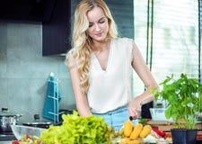 Ξανθή γυναίκα που προετοιμάζει ένα πιάτο γευμάτων στοκ εικόνες