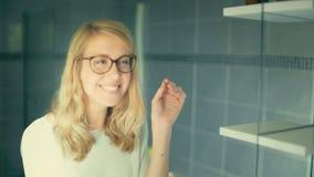 Ξανθή γυναίκα που προσπαθεί στα γυαλιά ευχαριστημένα από την αντανάκλασή της φιλμ μικρού μήκους
