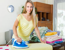 Ξανθή γυναίκα που σιδερώνει στο σπίτι Στοκ Φωτογραφία