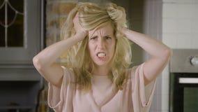 Ξανθή γυναίκα που τρελαίνεται τραβώντας την τρίχα της που βρυχείται στη κάμερα απόθεμα βίντεο
