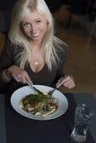 Ξανθή γυναίκα που τρώει τη σαλάτα για το μεσημεριανό γεύμα Στοκ Εικόνες