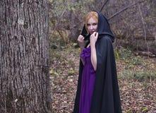 Ξανθή γυναίκα που φορά το μαύρο μανδύα στο δάσος φθινοπώρου Στοκ εικόνα με δικαίωμα ελεύθερης χρήσης