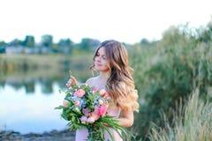 Ξανθή γυναίκα που φορά το ρόδινο φόρεμα με την ανθοδέσμη των λουλουδιών που στέκονται κοντά στη λίμνη Στοκ Φωτογραφία