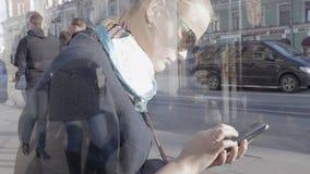 Ξανθή γυναίκα που χρησιμοποιεί το κινητό τηλέφωνο ενάντια στην αντανάκλαση γυαλιού των ανθρώπων που κινούνται κατά μήκος της οδού φιλμ μικρού μήκους