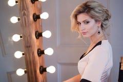 Ξανθή γυναίκα πολυτέλειας ομορφιάς Ελκυστικό νέο πρότυπο στην όμορφη συνεδρίαση φορεμάτων μπροστά από τον καθρέφτη, στο primp στοκ εικόνες με δικαίωμα ελεύθερης χρήσης